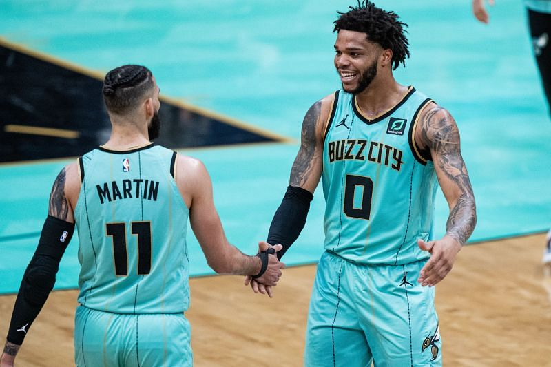 Cody Martin (#11) of the Charlotte Hornets is congratulated by Miles Bridges.