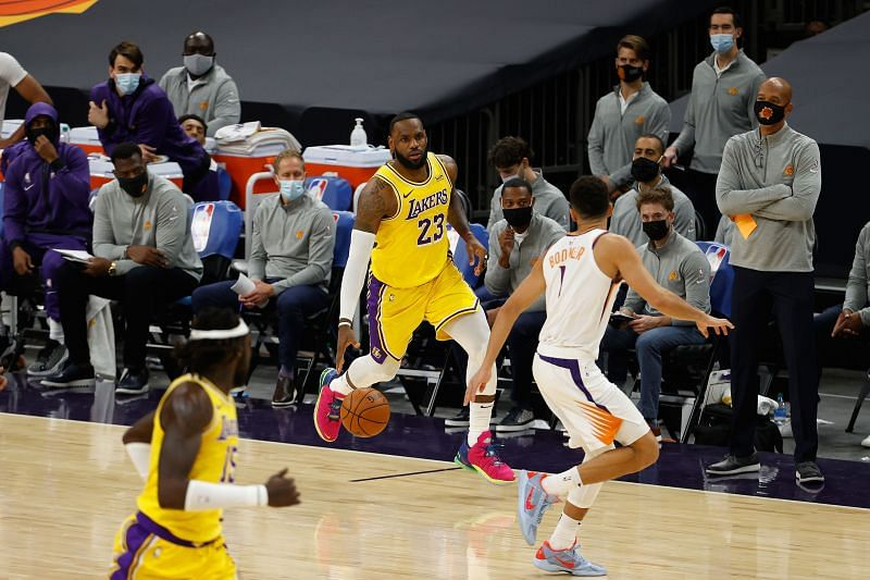 LeBron James #23 of the Los Angeles Lakers handles the ball against Devin Booker #1 of the Phoenix Suns.