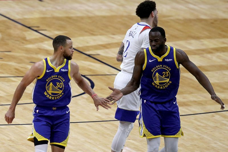 Stephen Curry #30 reacts with Draymond Green #23 after scoring a three point basket