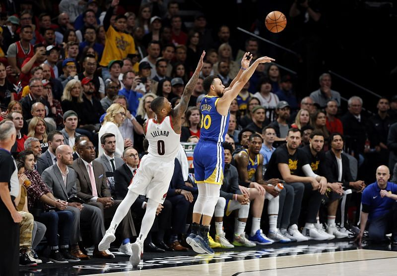 Stephen Curry shooting the ball while Damian Lillard tries to block him