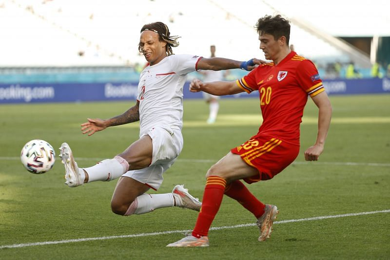 : Daniel James of Wales crosses the ball whilst under pressure from Kevin Mbabu of Switzerland