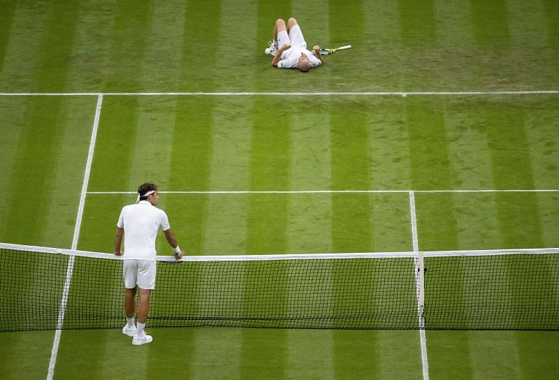 Roger Federer waits at the net as Adrian Mannarino takes a tumble