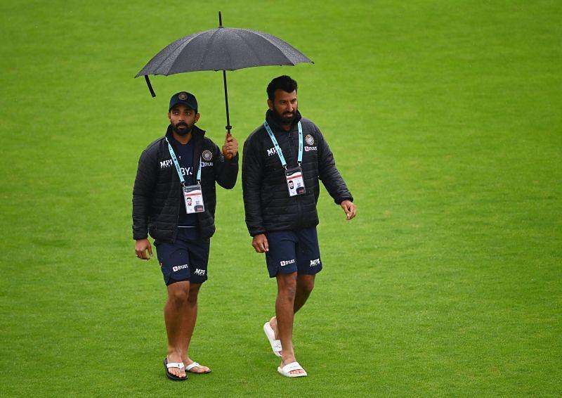 Ajinkya Rahane (L) and Chestehwar Pujara (R) walking on the outfield before start of play