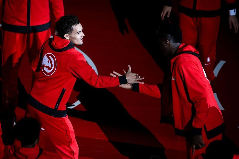 Trae Young #11 greets a teammate before the start of a game