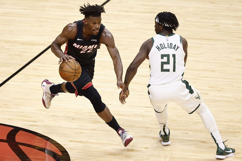 Jimmy Butler #22 of the Miami Heat dribbles up the court defended by Jrue Holiday #21 of the Milwaukee Bucks during the first quarter in Game Three of the Eastern Conference first-round NBA playoffs series
