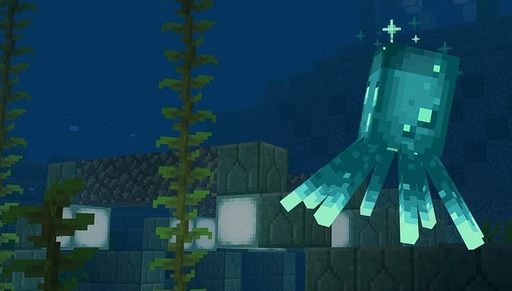 A glow squid swimming around an ocean monument (Image via Mojang)
