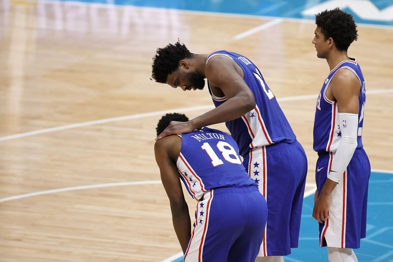 Shake Milton #18 is checked on by teammate Joel Embiid #21 following an injury