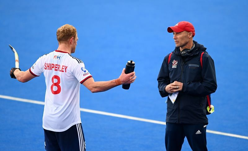 Great Britain head coach Danny Kerry (R) speaks to Rupert Shipperley during an FIH Pro League match