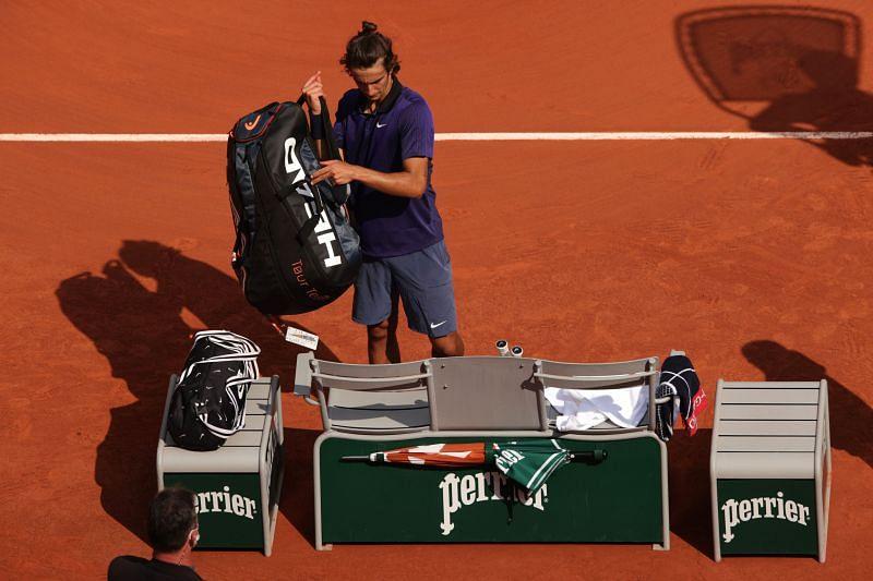 Lorenzo Musetti prepares to leave court after retiring against Novak Djokovic
