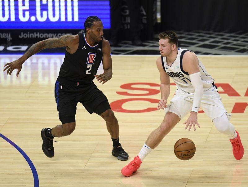 Luka Doncic #77 of the Dallas Mavericks dribbles away from Kawhi Leonard #2 of the LA Clippers