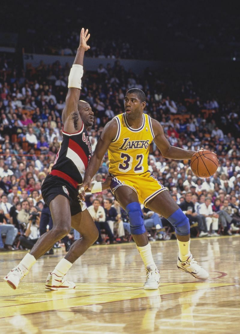 """Earvin """"Magic"""" Johnson #32 tries to dribble around Terry Porter #30."""