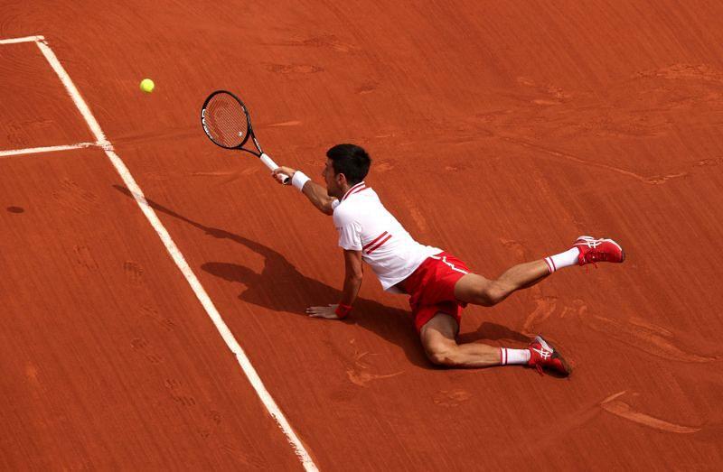 Novak Djokovic falls while returning