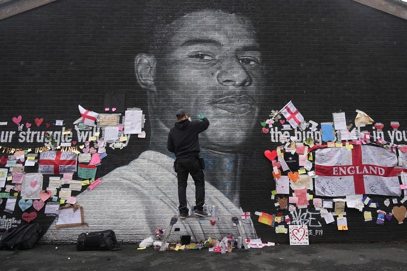 Defaced mural of Marcus Rashford being repaired by the artist in Manchester