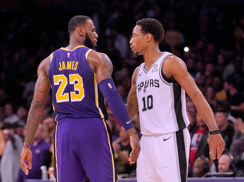 LeBron James #23 and DeMar DeRozan #10 talk on the court.