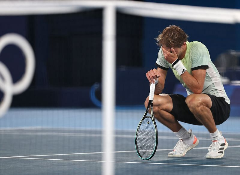 Alexander Zverev sinks to the turf after downing Novak Djokovic to reach the gold-medal match at the Tokyo Olympics.