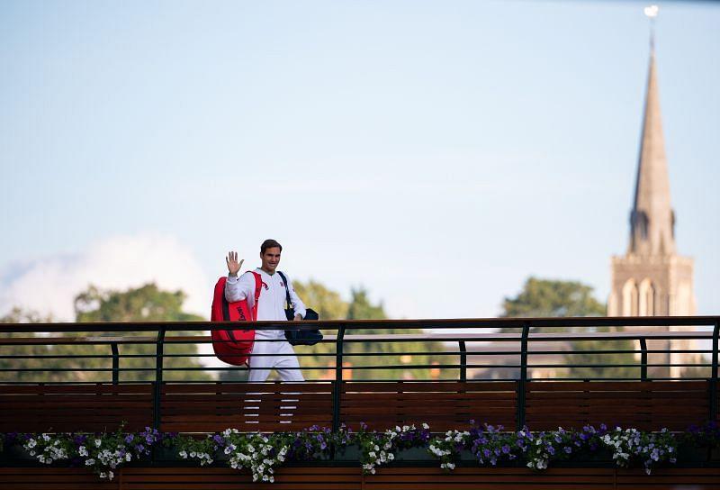 Roger Federer walking across the player