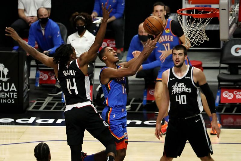 Theo Maledon (#11) of the Oklahoma City Thunder drives to the basket against Terance Mann (#14) of the LA Clippers