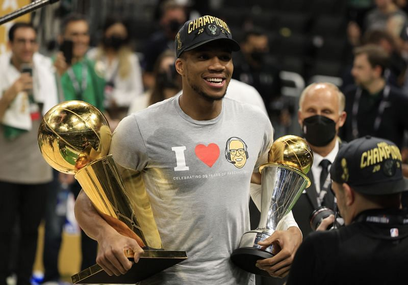 Giannis Antetokounmpo #34 holds the Bill Russell NBA Finals MVP Award and the Larry O'Brien Championship Trophy.
