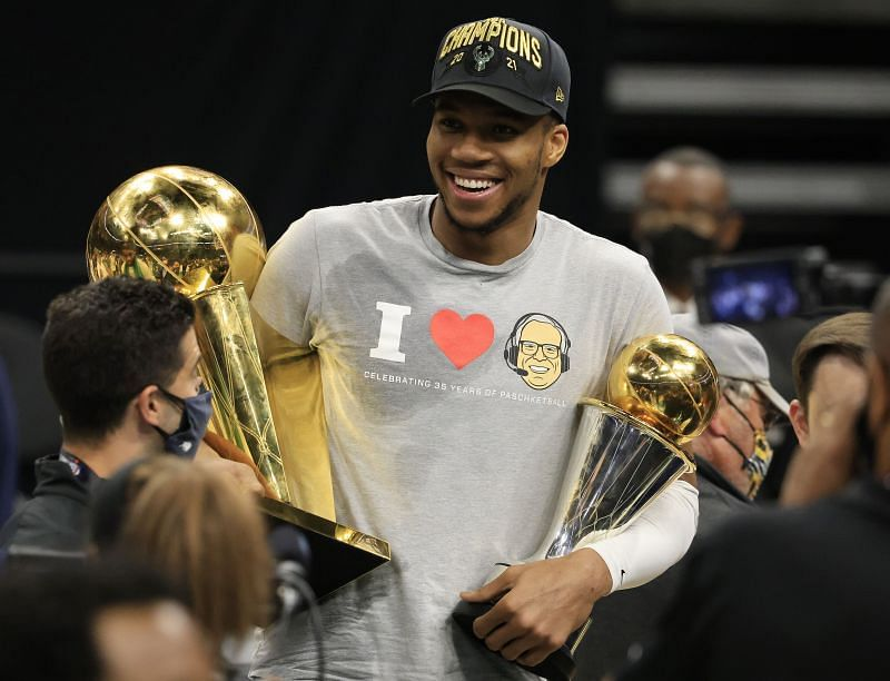 Giannis Antetokounmpo #34 of the Milwaukee Bucks holds the Bill Russell NBA Finals MVP Award and the Larry O'Brien Championship Trophy.