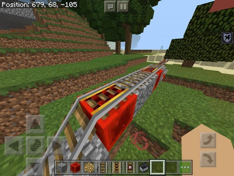 A railway with powered rails being powered with redstone blocks (Image via u/the_Smurf58skii on Reddit)