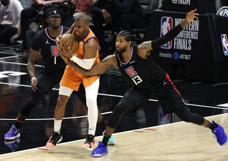 Chris Paul #3 of the Phoenix Suns protects the ball against Reggie Jackson #1 and Paul George #13 of the LA Clippers during the second half in Game Six of the 2021 NBA Playoffs Western Conference Finals