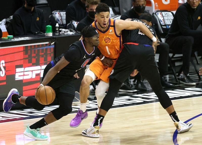 The LA Clippers' Reggie Jackson #1 drives past the Phoenix Suns' Devin Booker #1