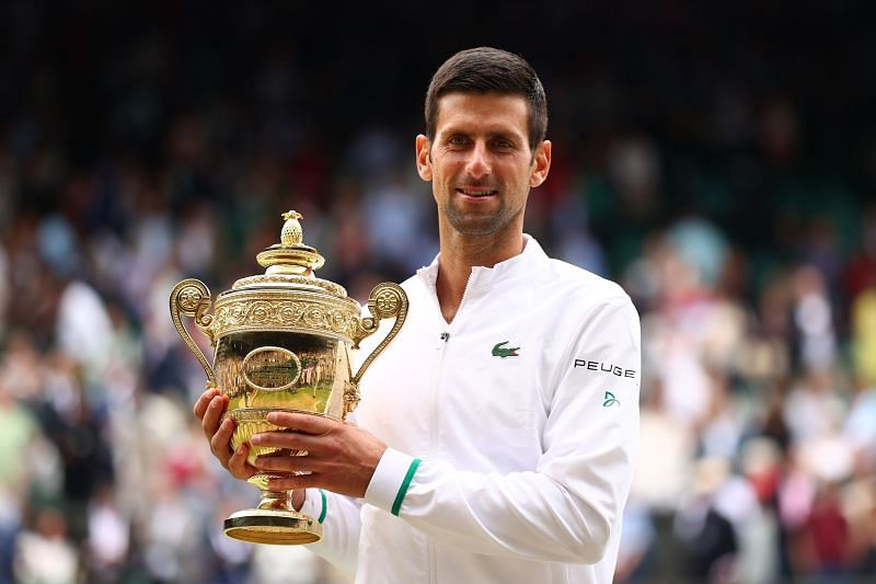 Novak Djokovic hoists aloft his Wimbledon 2021 title.