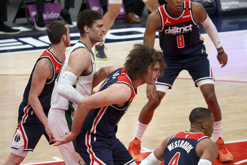 Twin brothers Robin Lopez #15 of the Washington Wizards and Brook Lopez #11 of the Milwaukee Bucks guard each other