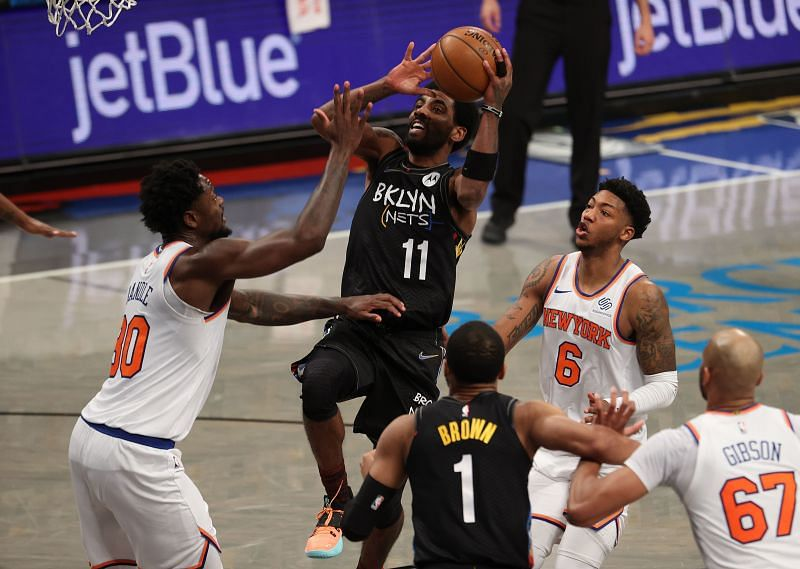 Kyrie Irving (#11) of the Brooklyn Nets shoots against Julius Randle (#30) of the New York Knicks.