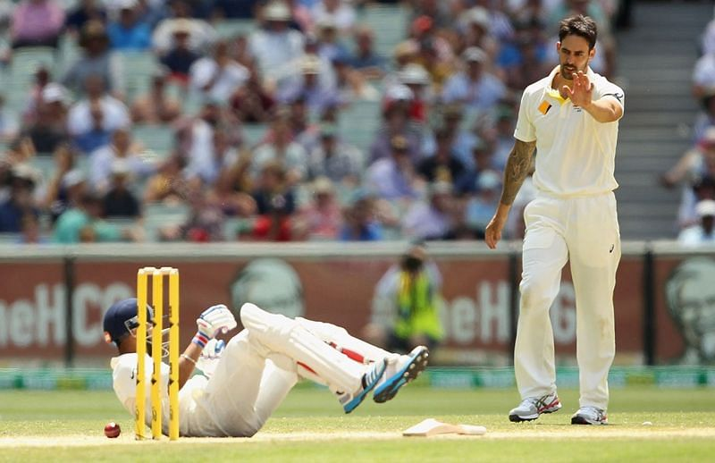 Kohli falls onto the ground after being hit by Mitchell Johnson in a run out attempt