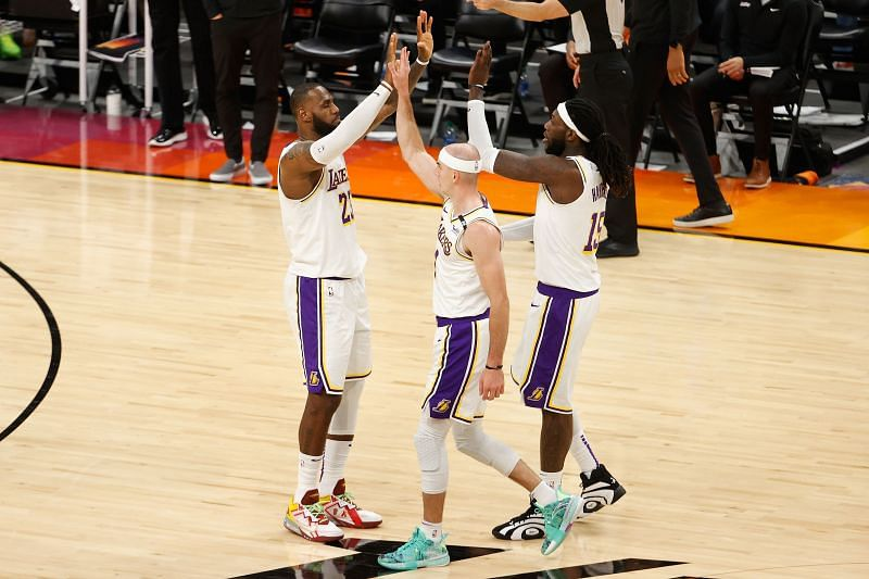 LeBron James #23 of the Los Angeles Lakers high fives Alex Caruso #4 and Montrezl Harrell #15