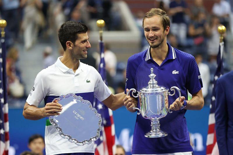 Novak Djokovic and Daniil Medvedev pose for photos during the 2021 US Open trophy ceremony