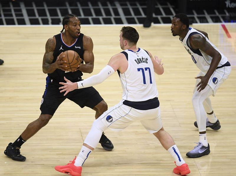 Kawhi Leonard (#2) of the LA Clippers looks to pass out of a double team from Luka Doncic (#77) and Dorian Finney-Smith (#10).