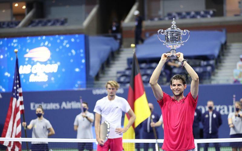 Dominic Thiem holding the 2020 US Open trophy aloft as beaten finalist Alexander Zverev looks on