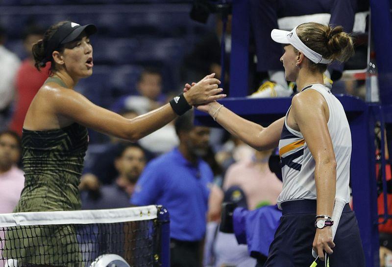 Garbine Muguruza (L) shakes hands with Barbora Krejcikova after their match at the 2021 US Open