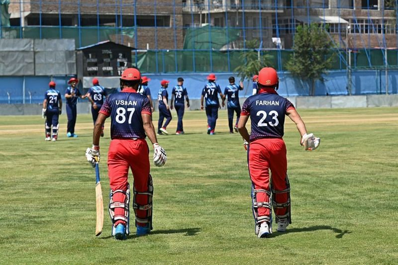 Afghanistan cricketers Usman and Farhan walk out into the middle