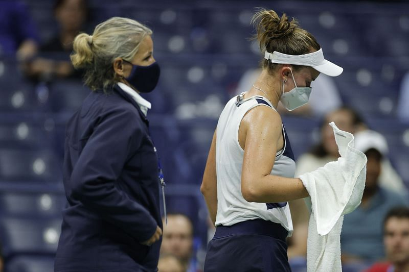 Barbora Krejcikova (R) walks off the court during the medical time-out