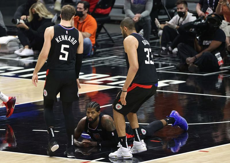 Paul George (#13) of the LA Clippers reacts as he falls to the court under Luke Kennard (#5) and Nicolas Batum (#33)