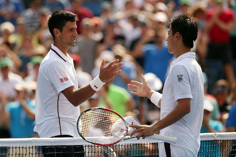Novak Djokovic (L) and Kei Nishiori at the 2014 US Open