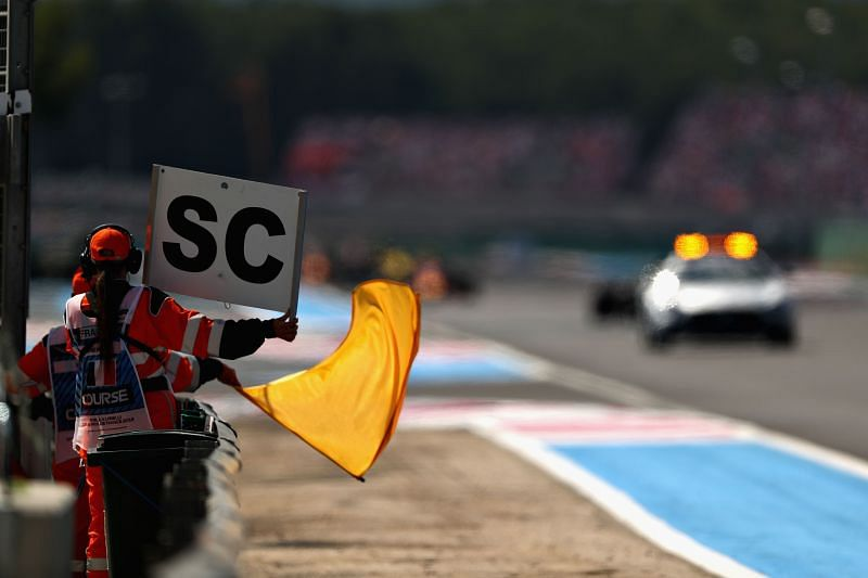 A marshal waves the yellow flag as the Safety Car leads the field during the 2018 French Grand Prix. (Photo by Dan Istitene/Getty Images)
