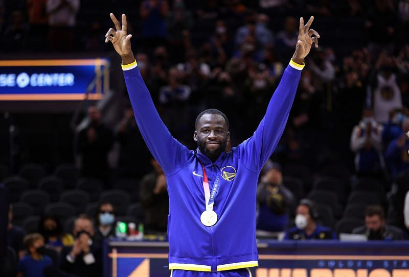 Draymond Green #23 of the Golden State Warriors waves to the crowd after he was presented with his Olympic gold medal before their game against the Denver Nuggets at Chase Center on October 06, 2021 in San Francisco, California.