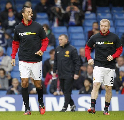 Rio Ferdinand (L) warms up with Paul Scholes (R), both wearing the T-shirt from Kick It Out
