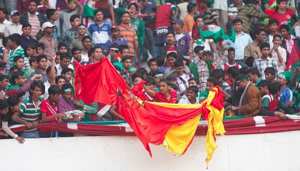 Mohun Bagan supporters burning an East Bengal flag in the stadium during I-League Match between Mohun Bagan and East Bengal on December 9, 2012 in Kolkata.