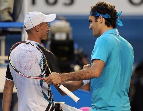 Roger Federer of Switzerland (R) shakes