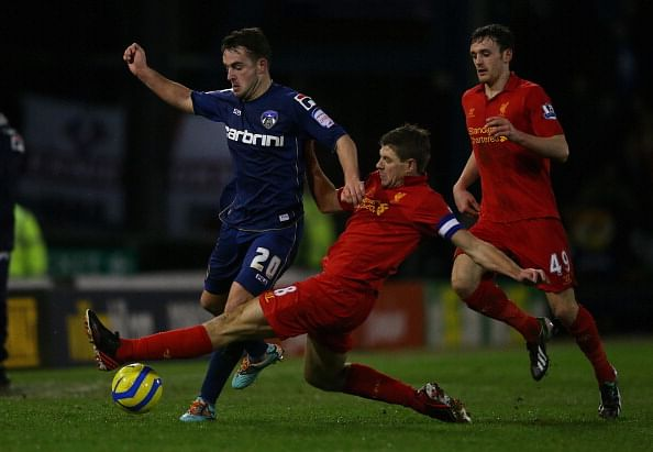 OLDHAM, ENGLAND - JANUARY 27:  Jose Baxter of Oldham competes with Steven Gerrard of Liverpool during the FA Cup with Budweiser Fourth Round match between Oldham Athletic and Liverpool at Boundary Park