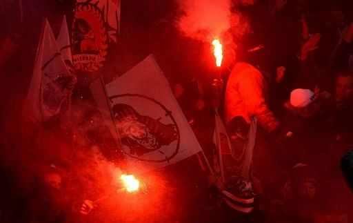 Hooligans hold flares during a Bundesliga football match in the German city of Leverkusen on January 19, 2013