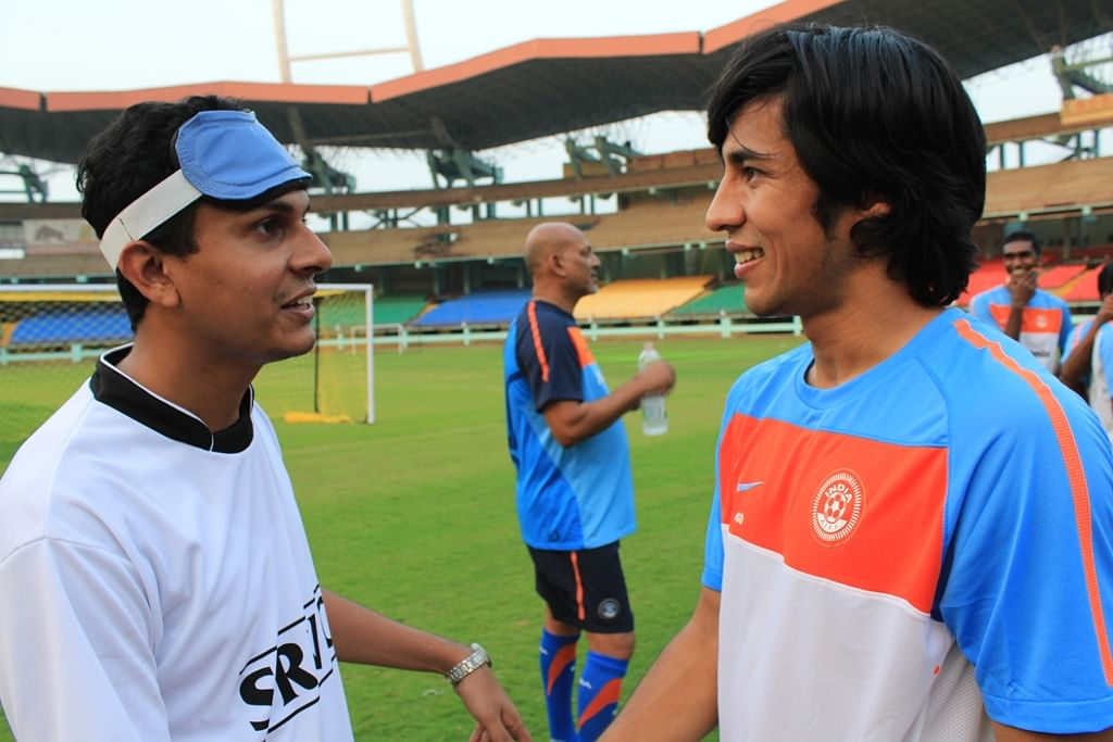 Arata Izumi chats with a blind footballer during his first practice session with the Indian National Team.