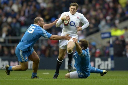 England full-back Alex Goode (C) fends off Italy