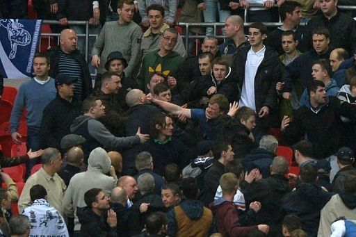 Millwall fans fight in the crowd during the FA Cup semi-finals at Wembley Stadium in north London, April 13, 2013