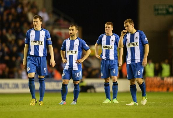 WIGAN, ENGLAND - MAY 07:  (L-R) Gary Caldwell, Shaun Maloney, James McCarthy and James McArthur of Wigan Athletic look despondent during the Barclays Premier League match between Wigan Athletic and Swansea City at DW Stadium on May 7, 2013 in Wigan, England.  (Photo by Laurence Griffiths/Getty Images)